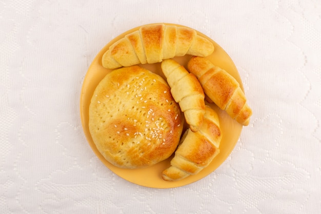 Widok z góry ciasta i rogaliki wewnątrz pomarańczowy talerz na białej podłodze