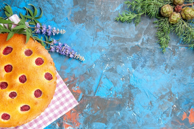 Widok z góry ciasta malinowego na gałęzi sosny ręcznik kuchenny na niebieskiej powierzchni