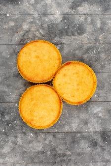 Widok z góry ciasta żółty gotowane słodko na szarej drewnianej rustykalnej podłodze
