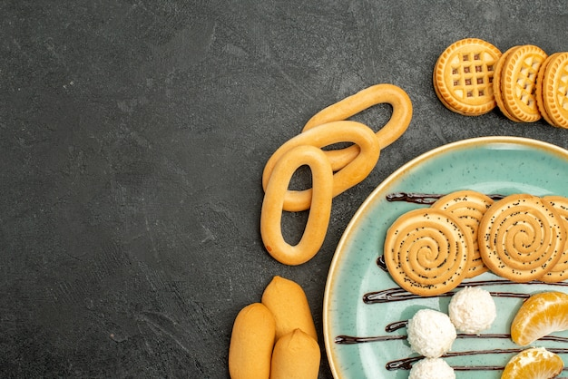 Widok z góry ciasteczka cukrowe z ciastkami i cukierkami na szarym biurku