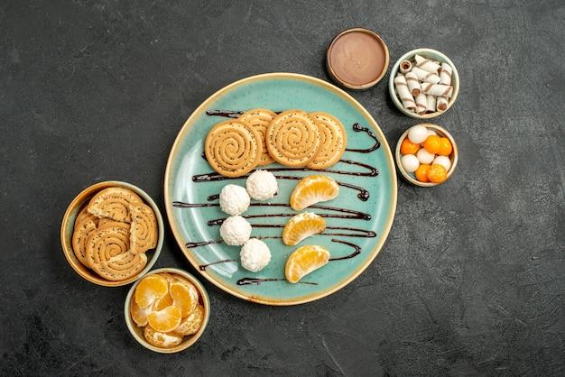 Widok z góry ciasteczka i cukierki z mandarynkami na szarym stole słodkie ciasteczka biszkoptowe