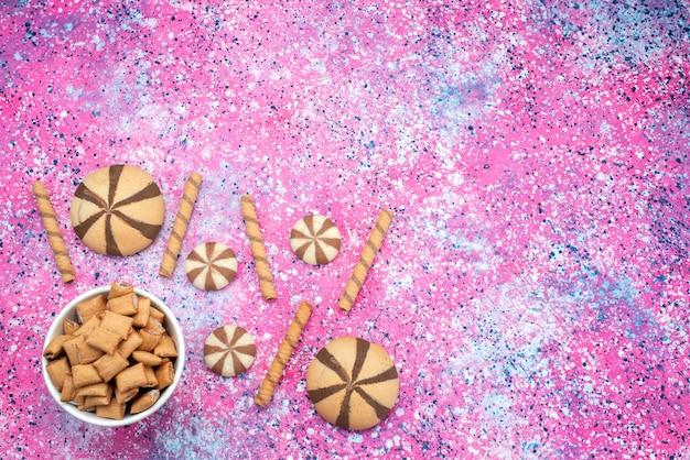 Widok z góry ciasteczka i krakersy na kolorowym biurku o słodkim, ostrym kolorze