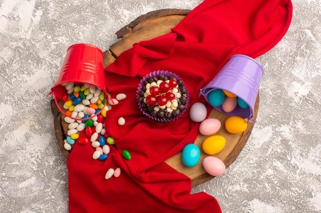 Widok z góry ciasteczka z cukierkami na czerwonej bibułce i jasnym tle cukierki słodkie ciasto do pieczenia czekolady