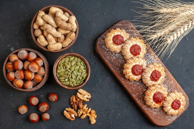 Widok z góry ciastka z dżemem na desce orzechy w miskach nasiona dyni orzechy włoskie orzechy laskowe kolce pszenicy na ciemnym tle