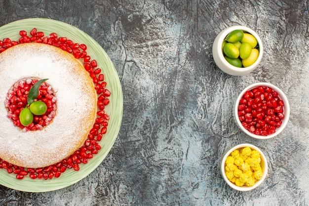 Widok z góry ciasto ciasto na talerzu trzy miseczki żółtych cukierków granat owoce cytrusowe