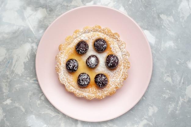 Widok z góry ciasto cukrowe w proszku z owocami wewnątrz talerza na jasnym stole ciasto owocowe piec cukier słodki ciastko