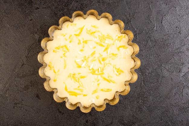 Widok z góry ciasto cytrynowe kwaśne pyszne egzotyczne ciasto piekarnicze słodkie na ciemnym biurku