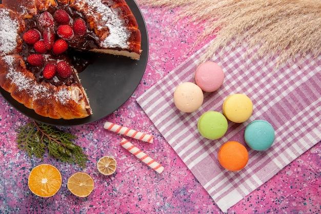 Widok z góry ciasto czekoladowe z truskawkami i makaronikami na różowym biurku słodkie ciasteczka biszkoptowe z cukrem