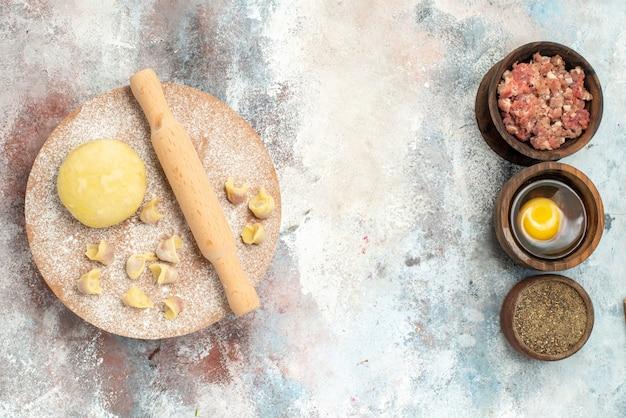 Widok z góry ciasto dushbara wałek do ciasta na desce do ciasta pionowe miski z żółtkiem papryki mięsnej na nagiej powierzchni wolne miejsce