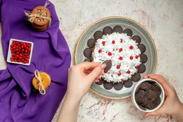 Widok z góry ciasto na talerzu ciasteczka przewiązane sznurkiem miska z jagodami na fioletowym szalu miska z czekoladą w kobiecej dłoni