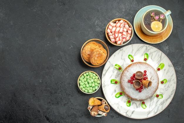 Widok z góry ciasto słodycze z jagodami słodycze gofry ciasteczka filiżanka herbaty