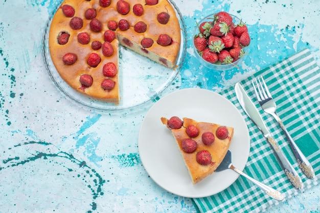 Widok z góry ciasto truskawkowe w plasterkach i całe pyszne ciasto wraz ze świeżymi czerwonymi truskawkami na jasnoniebieskim biurku ciasto jagodowe słodkie wypieki
