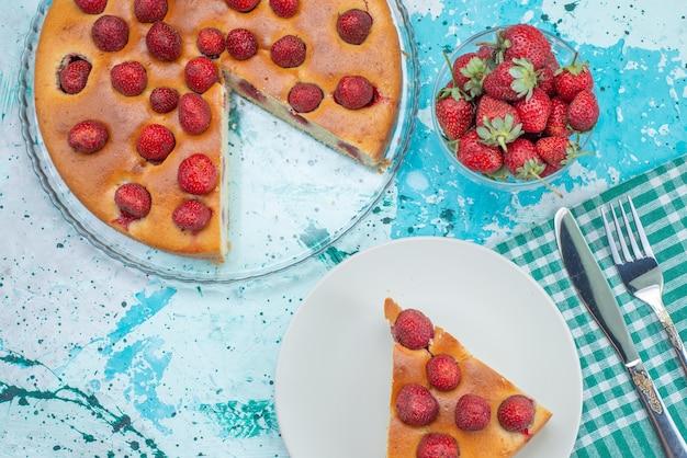 Widok z góry ciasto truskawkowe w plasterkach i całe pyszne ciasto wraz ze świeżymi czerwonymi truskawkami na jasnoniebieskim biurku ciasto jagodowe