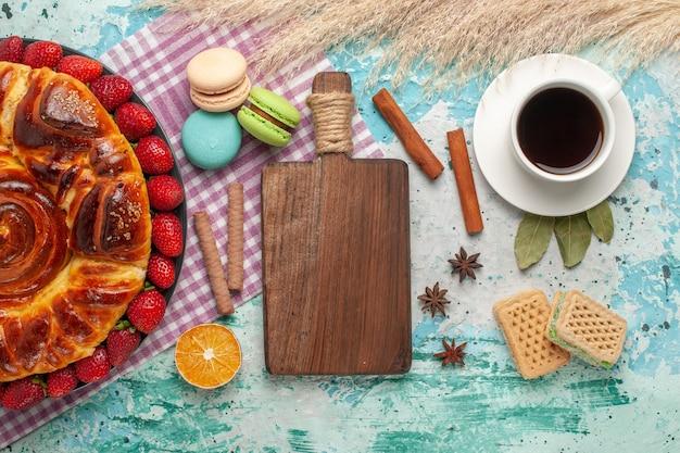 Widok z góry ciasto truskawkowe z ciasteczkami francuskimi makaronikami i filiżanką herbaty na jasnej powierzchni