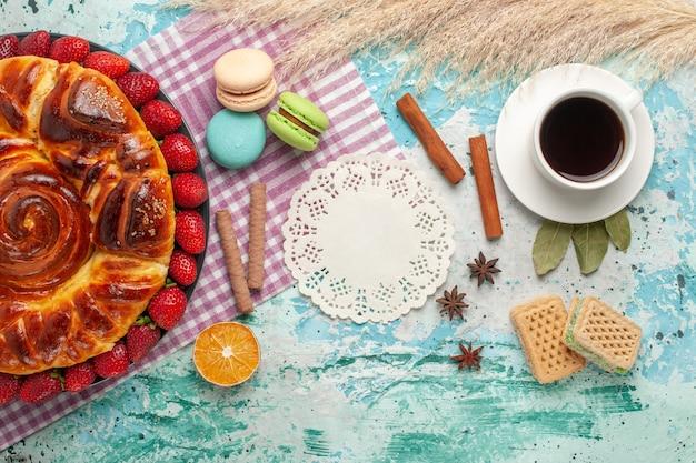 Widok z góry ciasto truskawkowe z ciasteczkami francuskimi makaronikami i filiżanką herbaty na jasnoniebieskiej powierzchni