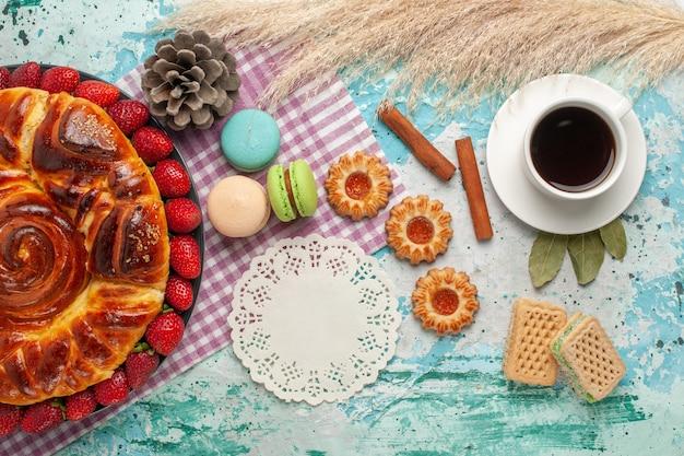 Widok z góry ciasto truskawkowe z ciasteczkami francuskimi makaronikami i filiżanką herbaty na niebieskim biurku