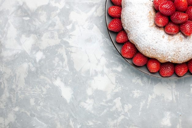 Widok z góry ciasto truskawkowe z cukrem pudrem na białym biurku