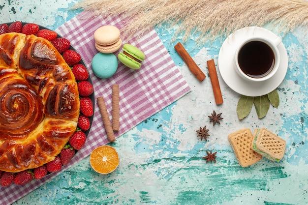 Widok z góry ciasto truskawkowe z goframi francuskimi macarons i filiżanką herbaty na niebieskiej powierzchni