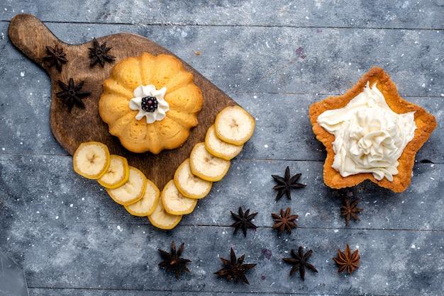 Widok z góry ciasto w kształcie gwiazdy ze śmietaną wraz z ciasteczkiem i pokrojonymi suszonymi owocami na lekkim stole ciasto biszkoptowe słodki cukier krem do pieczenia
