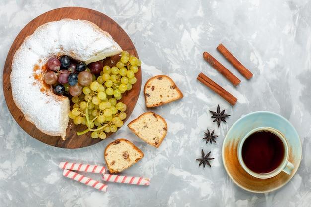 Widok z góry ciasto w proszku pyszne pieczone ciasto ze świeżymi winogronami i herbatą na białej powierzchni