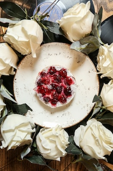 Widok z góry ciasto wiśniowe na talerzu z białymi różami w kole