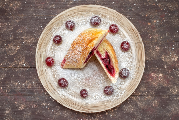 Widok z góry ciasto wiśniowe pyszne i słodkie w plasterkach ze świeżymi wiśniami wewnątrz talerza na brązowym drewnianym biurku ciasto biszkoptowe cukier słodkie wypieki