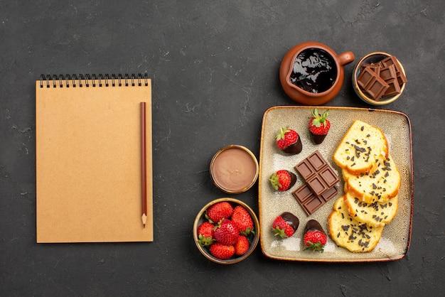 Widok z góry ciasto z czekoladowym notatnikiem i ołówkiem obok talerza z apetycznym ciastem z czekoladą i truskawkami oraz truskawkami i kremem czekoladowym w miseczkach