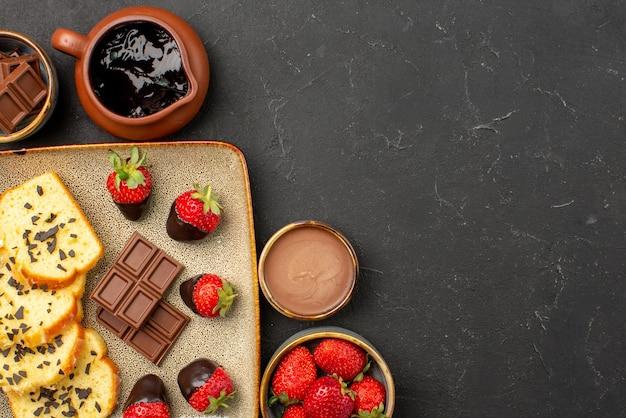 Widok z góry ciasto z truskawkami czekolada i truskawka w miseczkach oraz ciasto z truskawkami w czekoladzie na szarym talerzu po lewej stronie stołu