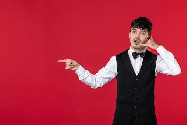 """Widok z góry ciekawskiego kelnera mężczyzny w mundurze z muszką i wykonującego gest """"zadzwoń do mnie"""", wskazując coś na prawą stronę."""
