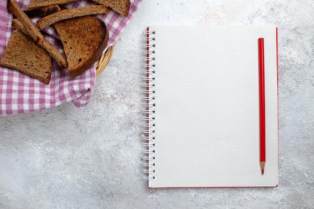Widok z góry ciemne bochenki chleba z notatnikiem na białym backgrond chleb bun copybook food