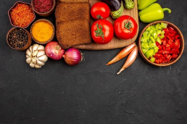 Widok z góry ciemne bochenki chleba z przyprawami pomidory i bakłażany na ciemnym tle sałatka zdrowie dojrzały posiłek warzywa dieta