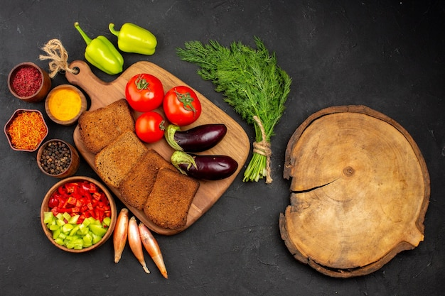 Widok z góry ciemne bochenki chleba z przyprawami pomidory i bakłażany na ciemnym tle sałatka zdrowie dojrzały posiłek