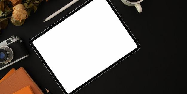 Widok z góry ciemne stylowe miejsce pracy z pustym ekranem tabletu i materiałów biurowych na czarny stół