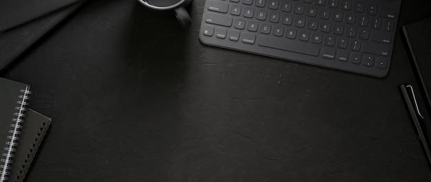 Widok z góry ciemnego obszaru roboczego z urządzeniem bezprzewodowym, materiałami biurowymi i miejscem do kopiowania