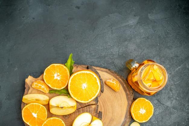 Widok z góry cięte jabłka i pomarańcze na koktajlu na desce na ciemnym tle