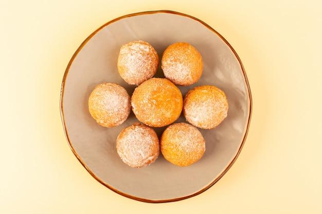 Widok z góry cukier puder w proszku okrągłe słodkie pieczone pyszne małe ciasta wewnątrz okrągłej platformy i kremowe tło piekarnia słodki herbatnik