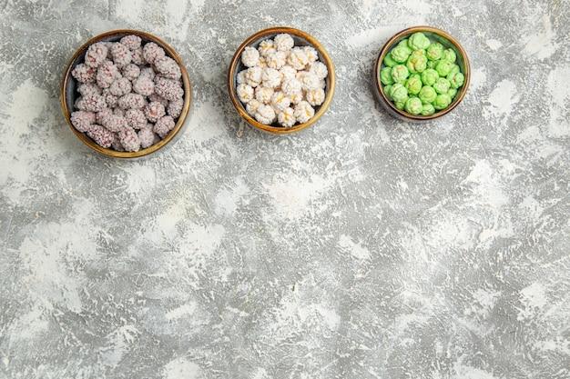 Widok z góry cukierki cukrowe wewnątrz małych talerzyków na jasnym białym tle candy candy sugar bonbon słodkie ciasteczko