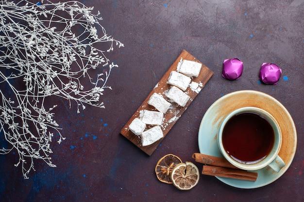 Widok z góry cukierków w proszku, pyszny nugat z filiżanką herbaty na ciemnej powierzchni