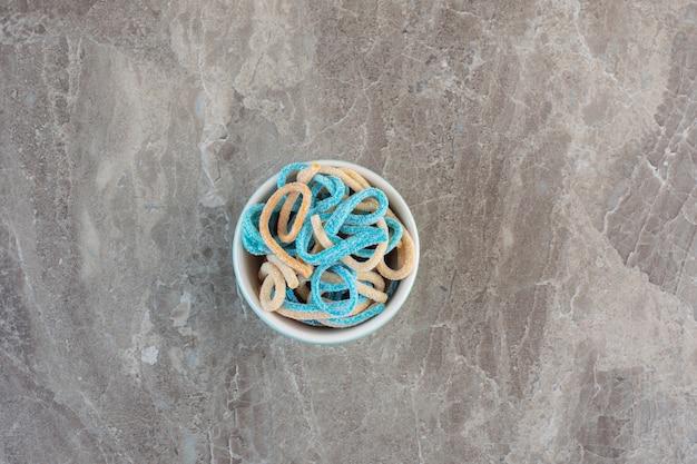 Widok z góry cukierków wstążki w misce na szarym tle.