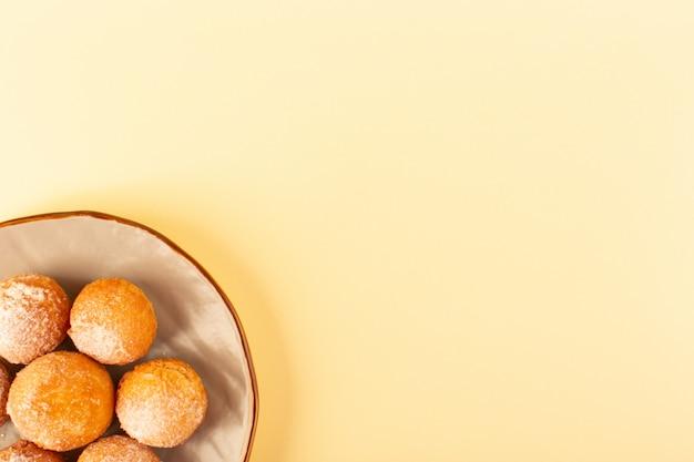 Widok z góry cukrowe ciastka w proszku okrągłe słodkie pieczone pyszne ciasteczka wewnątrz okrągłej platformy i śmietany