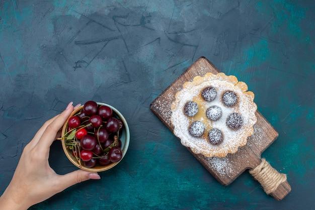 Widok z góry cukrowe ciasto w proszku z wiśniami w środku i wraz ze świeżymi wiśniami na ciemnoniebieskim tle ciasto owocowe herbatniki słodkie