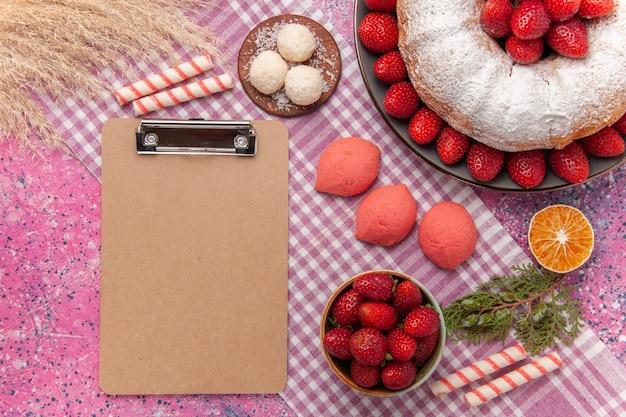Widok z góry cukru pudru ciasto truskawkowe z różowymi ciastami na różowo