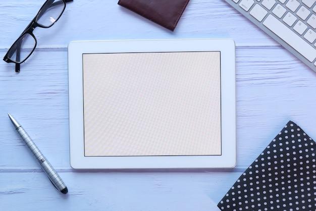 Widok z góry cyfrowego tabletu z dostawcami biurowymi na stole.