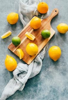 Widok z góry cytryny i limonki owoców cytrusowych na desce na niebieskim betonie