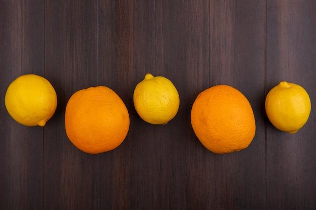Widok z góry cytryny z pomarańczami na tle drewna