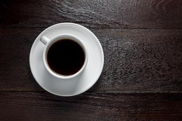 Widok z góry czarna kawa na drewnianym stole z kopi? miejsca.