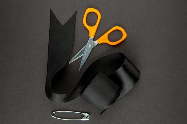 Widok z góry czarna kokarda z nożyczkami na szarym tle