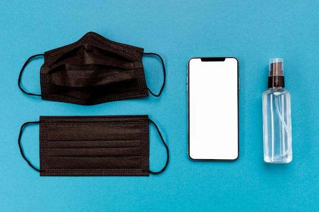 Widok z góry czarne maski medyczne z pustym telefonem