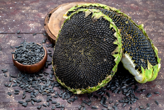 Widok z góry czarne pestki słonecznika świeże i smaczne na brązowym ziarnie słonecznika na biurku