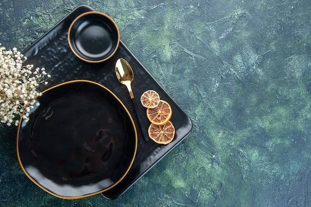 Widok z góry czarne talerze różnej wielkości i kształtu na ciemnym tle kolacja obiad srebrna obsługa restauracji sztućce jedzenie